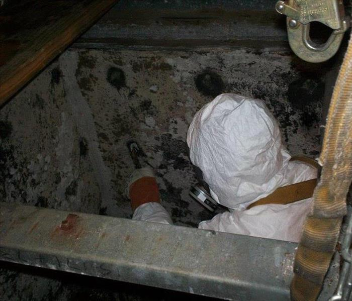 An Air Duct Cleaning Specialist inside of a commercial HVAC Trunk System